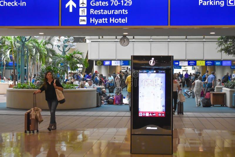 Женщина идя с чемоданом, экраном центра для посетителей и взглядом сверху знака регистрации голубого на международном аэропорте О стоковые изображения rf