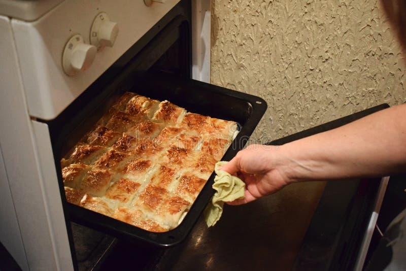 Женщина извлекая поднос пирога от печи в кухне стоковые изображения