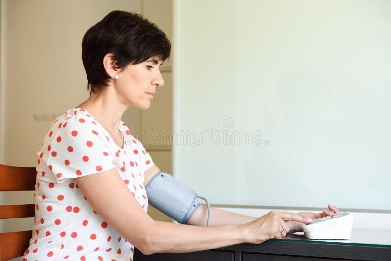 Женщина измеряя ее собственное кровяное давление дома стоковая фотография