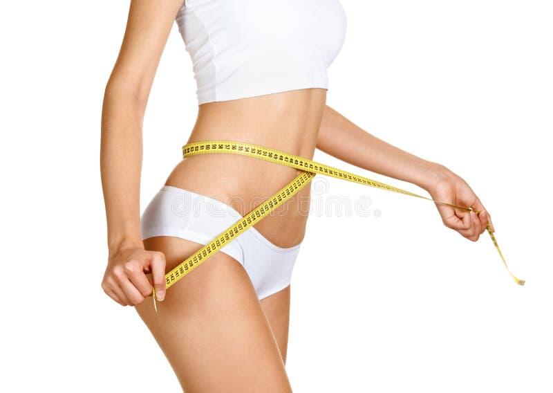 Женщина измеряя ее талию. Совершенное тонкое тело стоковое фото rf