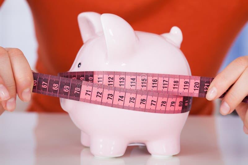 Женщина измеряя Piggybank с лентой измерения стоковая фотография rf