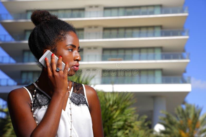 Женщина изображения запаса говоря на взгляде сотового телефона Афро-американском стоковое изображение rf