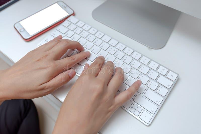 Женщина из офиса печатает на клавиатуре, закрывается, смартфон стоковые изображения rf