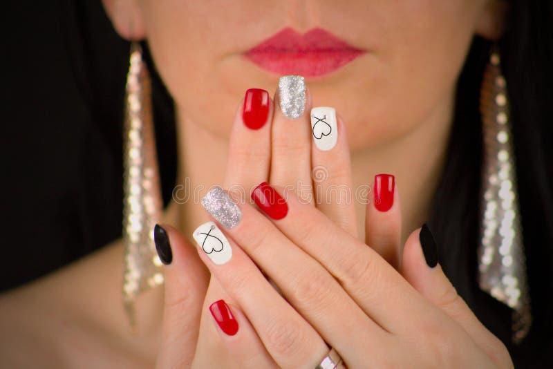 ЖЕНЩИНА ИМЕЕТ КРАСНЫЙ, черный, блестящий серебр и белые ногти с сердцем Она держит ее ладони перед ее стороной Она имеет красные  стоковое изображение rf