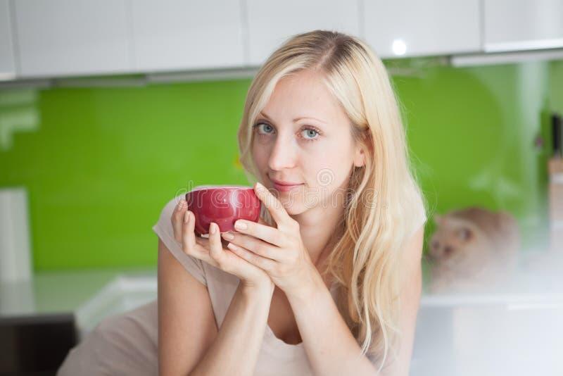 Женщина имеет перерыв на чашку кофе дома стоковые фото