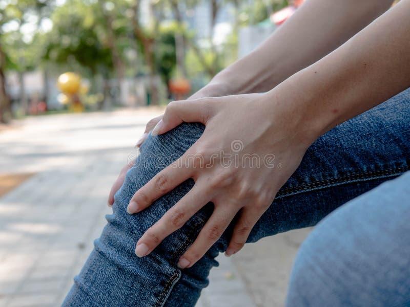 Женщина имея боль колена в медицинском офисе Перерывы и растяжения непознаваемые, здравоохранение стоковое изображение rf