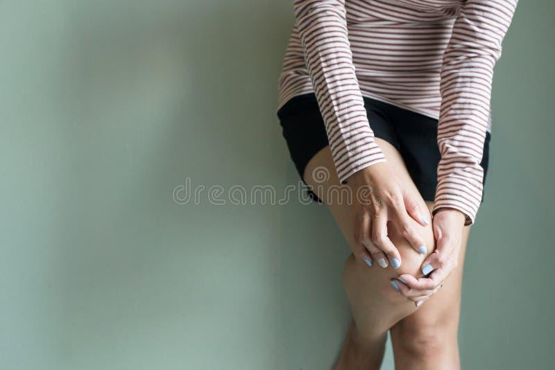 Женщина имея боль колена, женское чувствуя воспаление и тягостное, слабое mussle, копирует космос для текста стоковая фотография