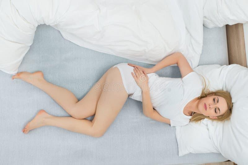 Женщина имея боль в спине стоковые фото