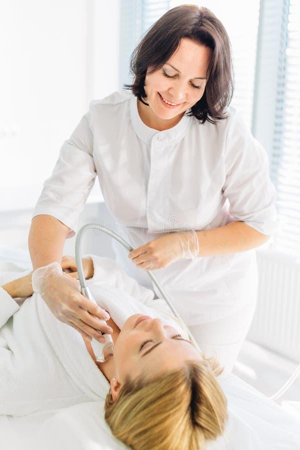 Женщина имея возбуждающую лицевую обработку от терапевта стоковое изображение rf