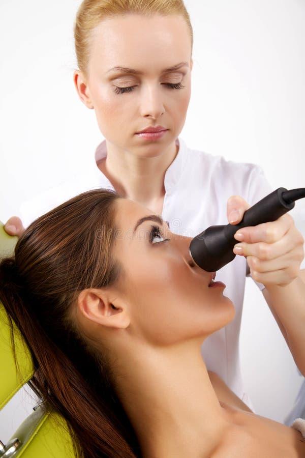 Женщина имея возбуждающую лицевую обработку от терапевта стоковые изображения