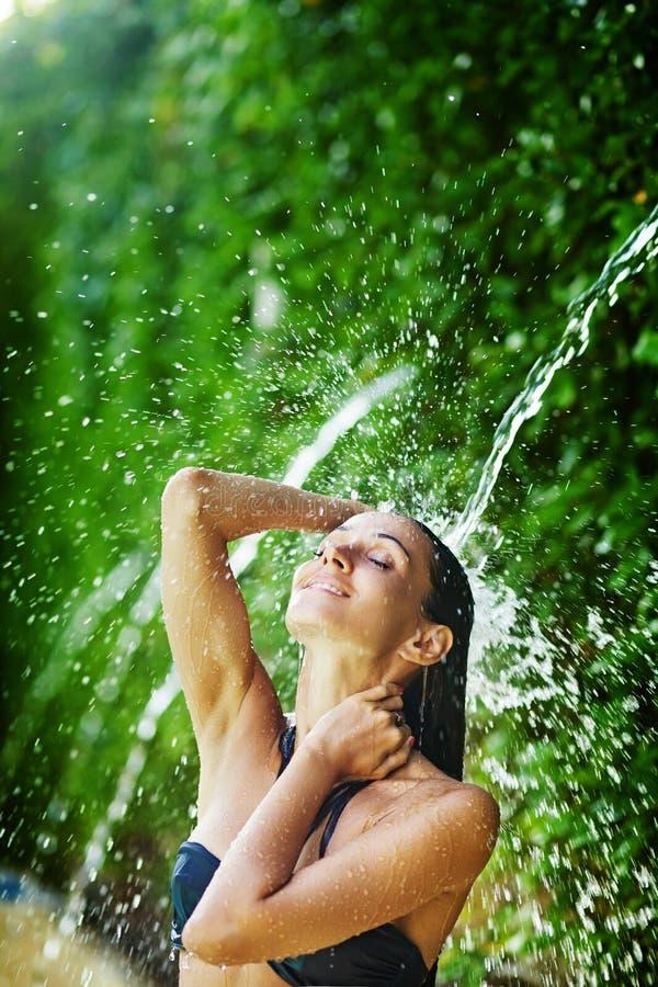 Женщина имея ливень под тропическим водопадом стоковые фотографии rf