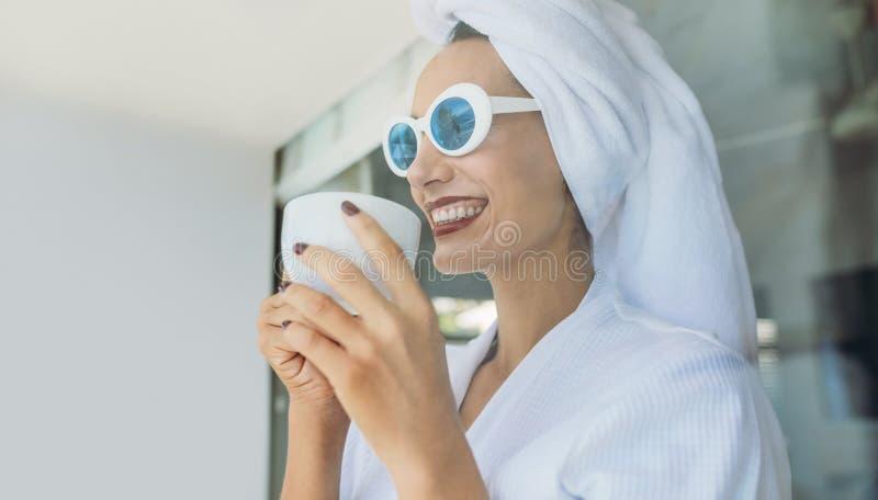 Женщина имея кофе после ливня стоковая фотография