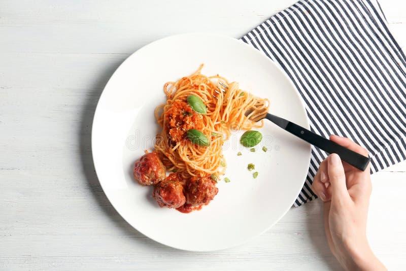 Женщина имея макаронные изделия с фрикадельками и томатным соусом стоковые изображения rf