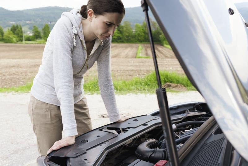 Женщина имея нервное расстройство автомобиля и вытаращить на двигателе стоковое изображение rf