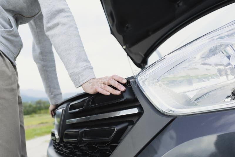Женщина имея нервное расстройство автомобиля и вытаращить на двигателе стоковые фото