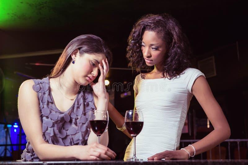 Женщина имея пить и утешая ее подавленного друга стоковая фотография