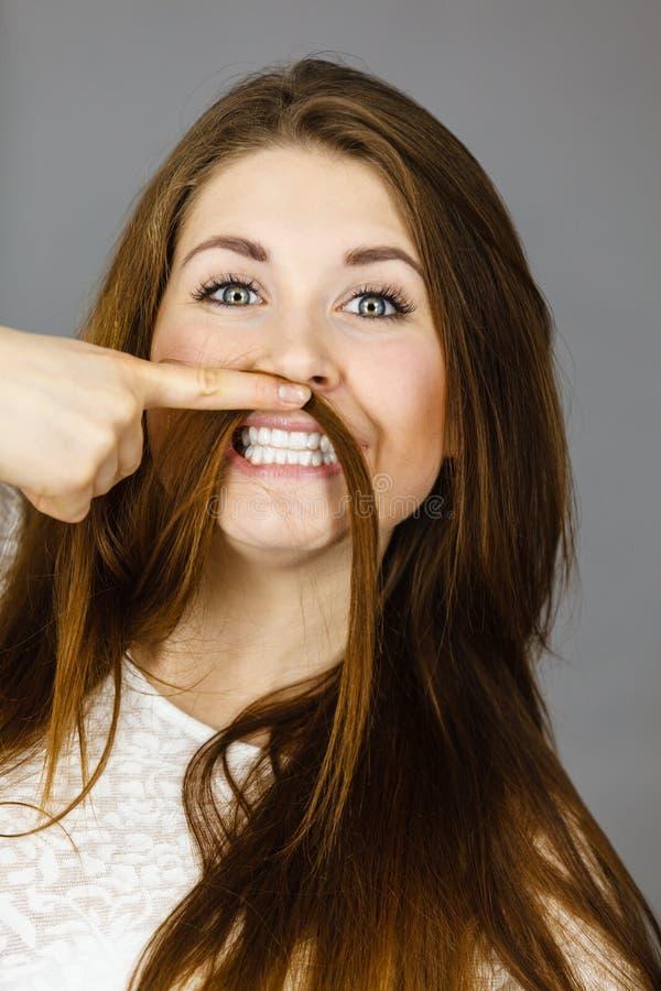 Женщина имея потеху с ее волосами делая усик стоковые изображения rf
