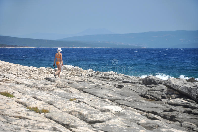 Женщина имея прогулку на пляже в swimwear стоковые фото