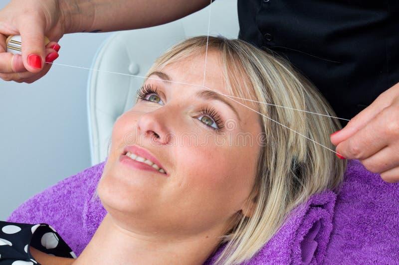 Женщина имея продевать нитку процедуру удаления волос стоковая фотография rf