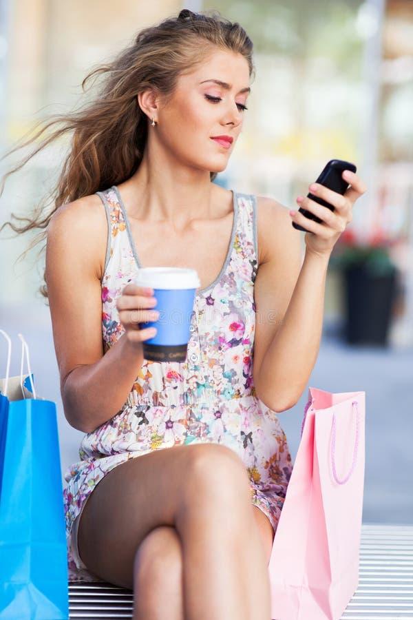 Женщина имея пролом от покупок стоковые изображения