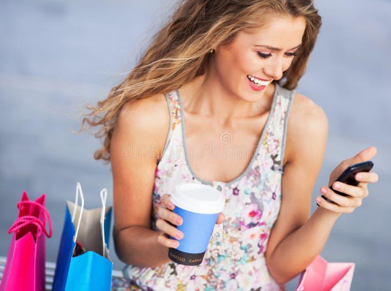 Женщина имея пролом от покупок стоковая фотография rf