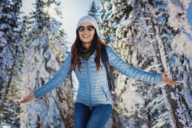 Женщина имея счастливую прогулку зимы в снеге покрыла древесины стоковое изображение