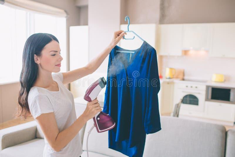 Женщина испаряется голубая рубашка в комнате Она держит малый утюг потока в руке Брюнет сконцентрировано на работе стоковая фотография