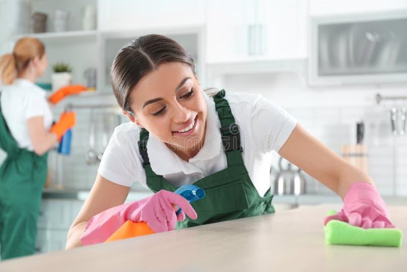 Женщина используя ветошь и спрейер для очищая таблицы с коллегой стоковая фотография