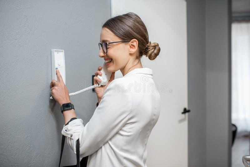 Женщина используя внутренную связь квартиры стоковое изображение rf