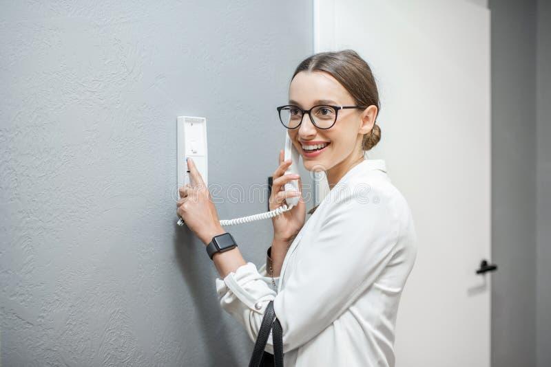 Женщина используя внутренную связь квартиры стоковые фотографии rf