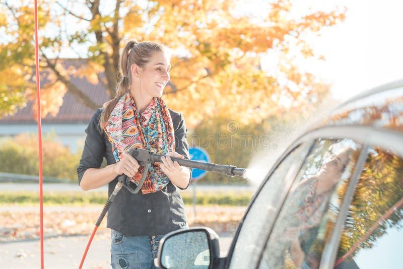 Женщина используя высокое сопло давления для того чтобы очистить ее автомобиль стоковое фото rf