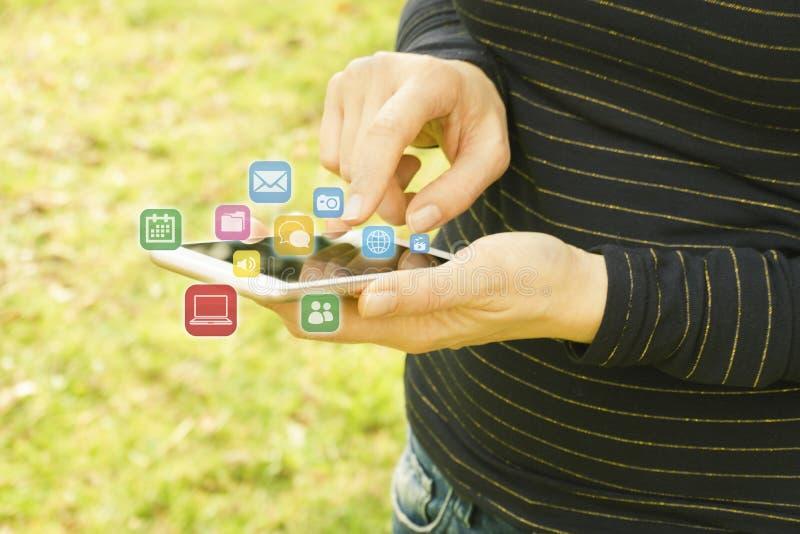 Женщина используя ее мобильный телефон на открытом воздухе стоковое фото rf