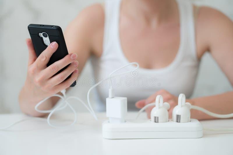 Женщина используя и поручающ смартфон Энергия на всю жизнь стоковые изображения