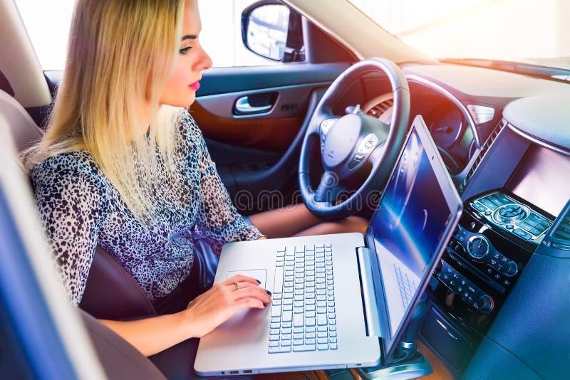 Женщина используя компьтер-книжку в ее автомобиле стоковое фото