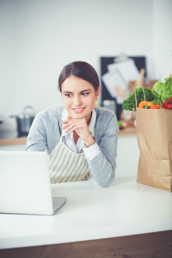 Женщина используя компьтер-книжку дома в кухне стоковые изображения