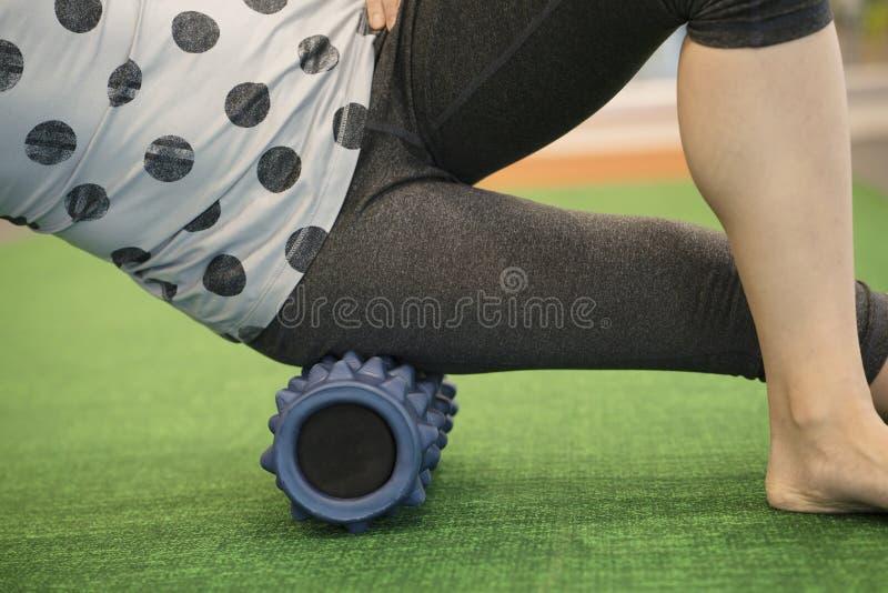 Женщина используя крен пены на ее ноге для того чтобы выпустить напряжение стоковое фото