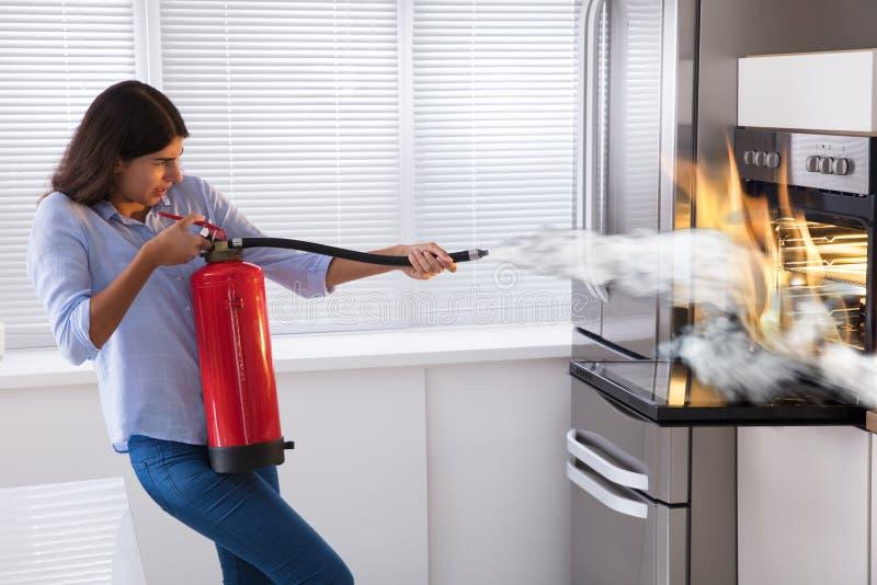 Женщина используя огнетушитель для того чтобы положить вне огонь от печи стоковые фото