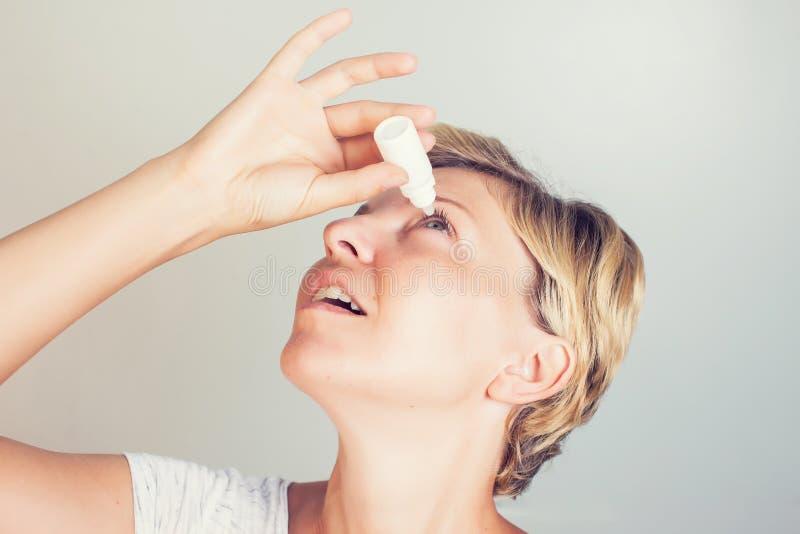 Женщина используя падения глаза в глазах стоковые фото