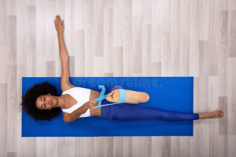 Женщина используя пояс йоги пока делающ тренировку стоковая фотография