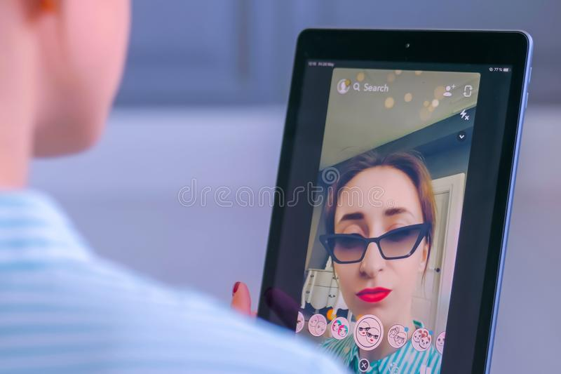 Женщина используя приложение послания мультимедиа Snapchat с лицевым щитком гермошлема на планшете стоковое фото rf