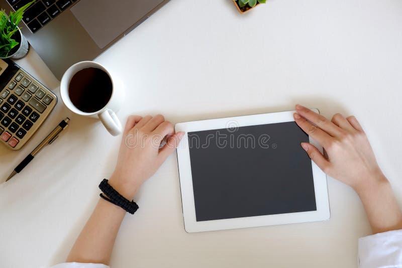 женщина используя таблетку на столе офиса стоковое фото rf