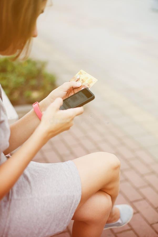 Женщина используя телефон и карточку для ходить по магазинам стоковая фотография rf