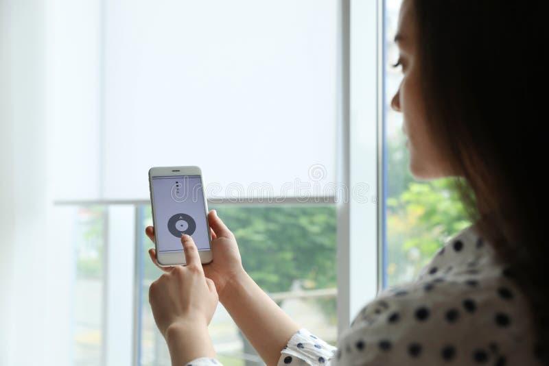 Женщина используя умное домашнее применение по телефону к шторкам окна контроля стоковая фотография