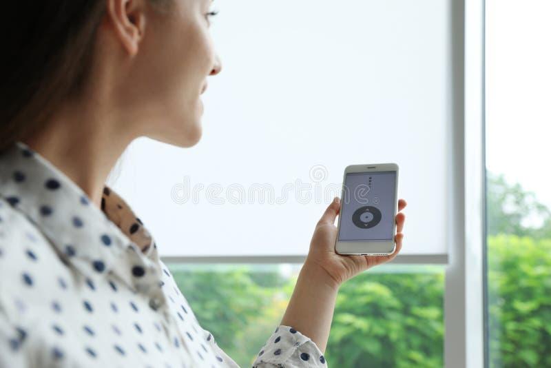 Женщина используя умное домашнее применение по телефону к шторкам окна контроля стоковые изображения