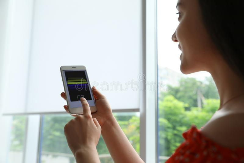 Женщина используя умное домашнее применение по телефону к шторкам окна контроля стоковое фото