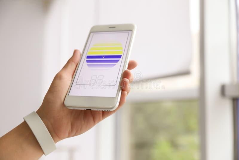 Женщина используя умное домашнее применение по телефону к шторкам окна контроля внутри помещения, крупный план стоковые изображения rf