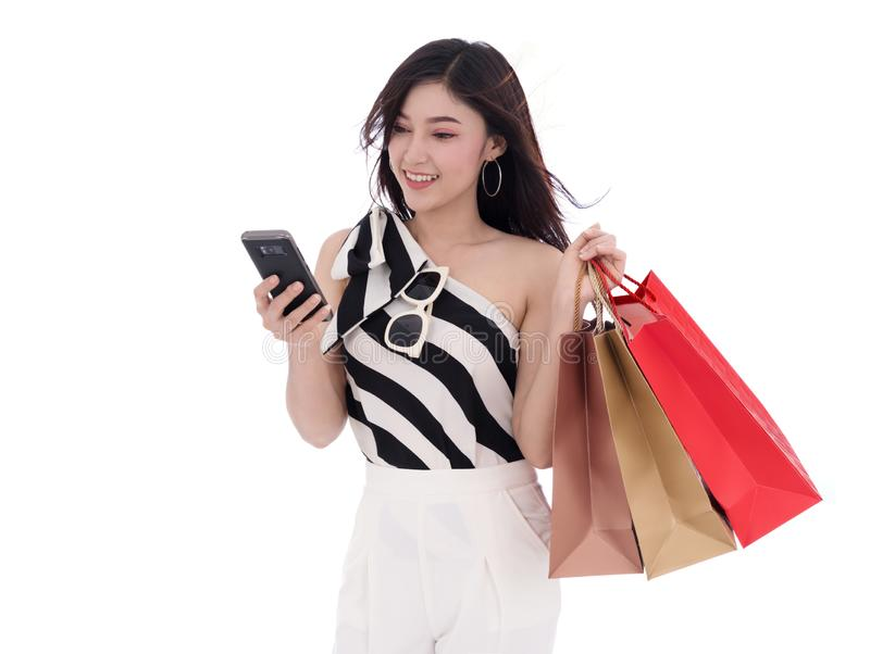 Женщина используя smartphone и держащ хозяйственные сумки изолированный на whi стоковая фотография rf