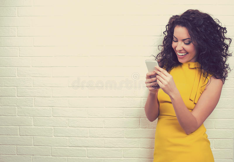 Женщина используя высокоскоростную интернет-связь отправляя СМС на умном телефоне стоковая фотография