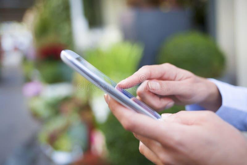 Женщина используя ее мобильный телефон перед флористом стоковые изображения