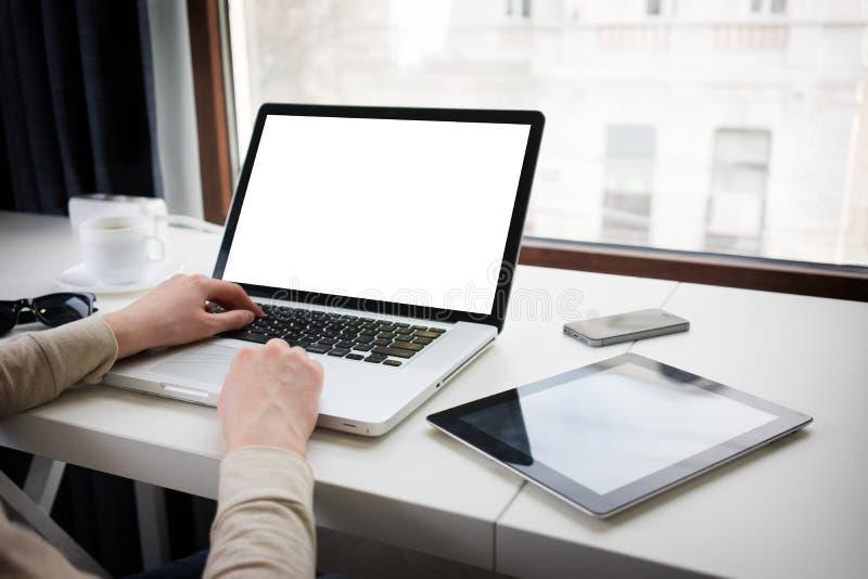 Женщина используя компьтер-книжку рядом с окном стоковые фото